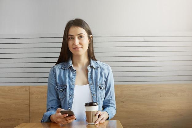 Garota jovem e atraente com cabelos escuros e roupas elegantes, sentado no café, tomando café e olhando fotos de férias em seu smartphone.
