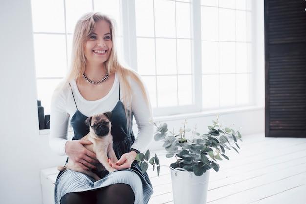 Garota jovem e atraente com cachorro pug fofo nas mãos