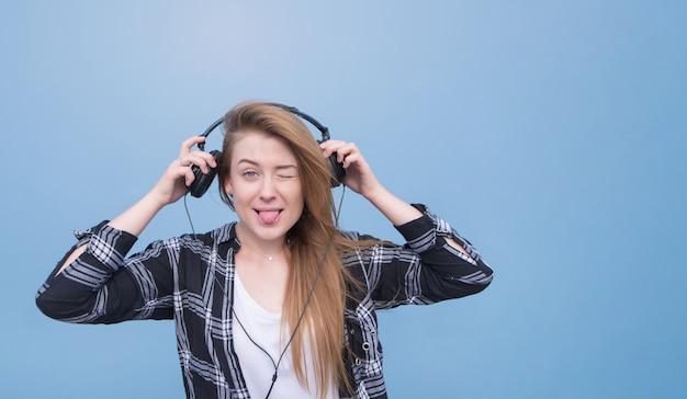Garota jovem e atraente com fones de ouvido é sobre um fundo azul e olha para a câmera.