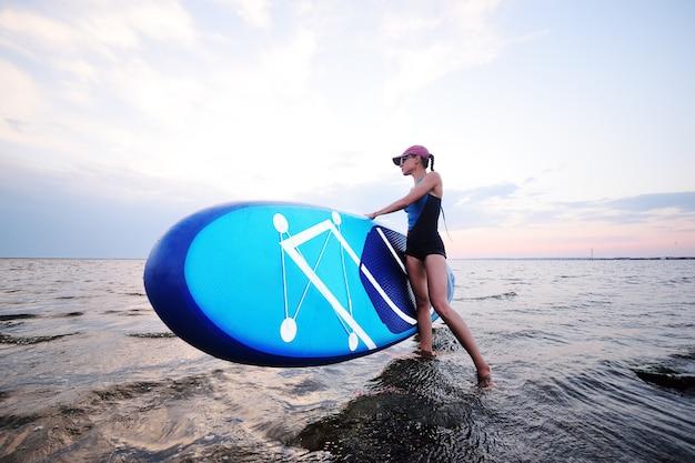 Garota jovem e atraente com placa sup no fundo do mar e pôr do sol