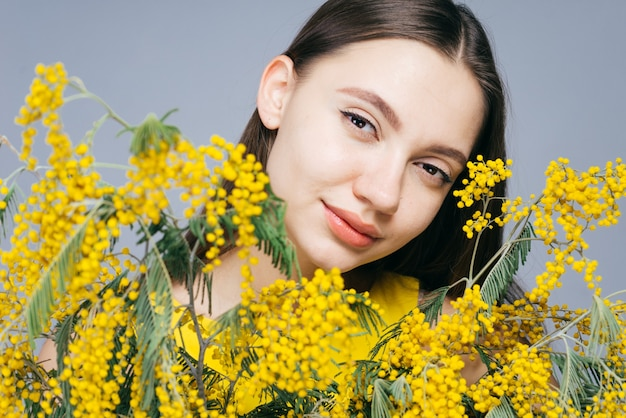 Garota jovem e atraente curtindo a primavera, segurando um buquê de mimosa amarela