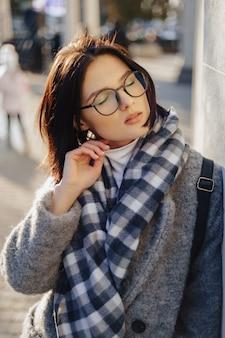 Garota jovem e atraente de óculos com um casaco andando em um dia ensolarado