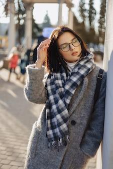 Garota jovem e atraente de óculos em um casaco andando em um dia ensolarado