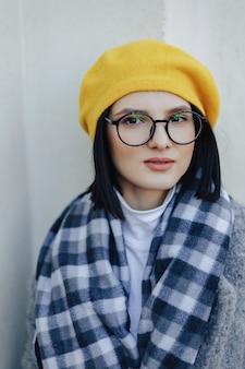 Garota jovem e atraente de óculos no casaco e boina amarela