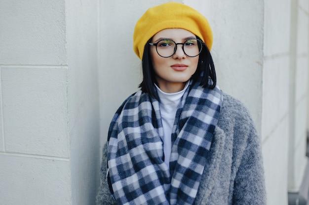 Garota jovem e atraente em copos no casaco e amarelo