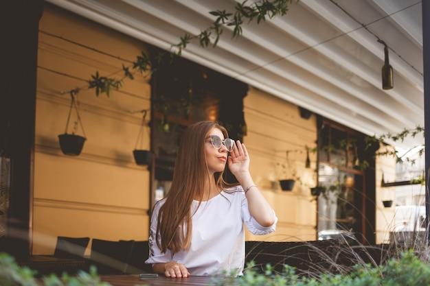 Garota jovem e atraente em copos se senta em uma mesa de restaurante