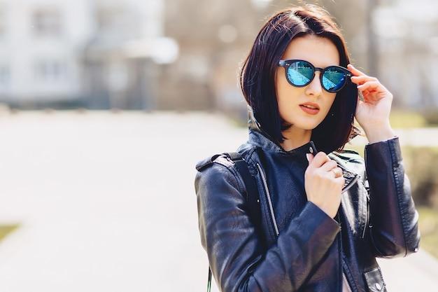 Garota jovem e atraente em óculos de sol em dia ensolarado
