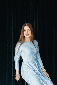 Garota jovem e atraente em um fundo de veludo escuro com um vestido azul