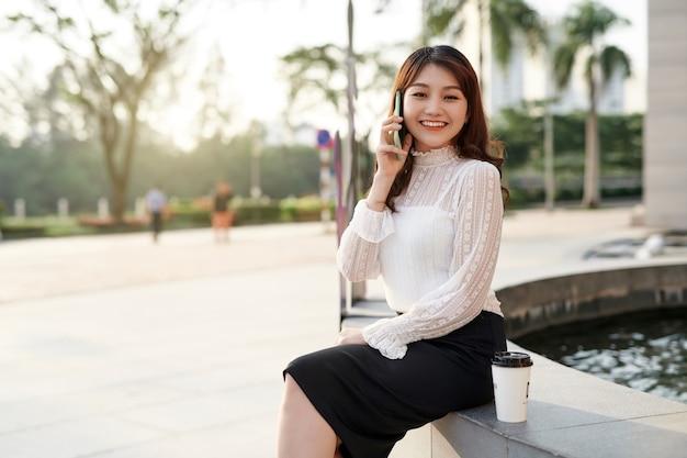 Garota jovem e atraente está sorrindo e sentado com uma caneca de café e um smartphone.