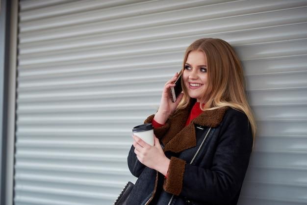 Garota jovem e atraente. falando no celular no parque. jovem atraente, conversando com seus amigos pelo celular e tomando café