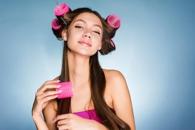 Garota jovem e atraente faz um penteado da moda com rolos de cabelo e pentes