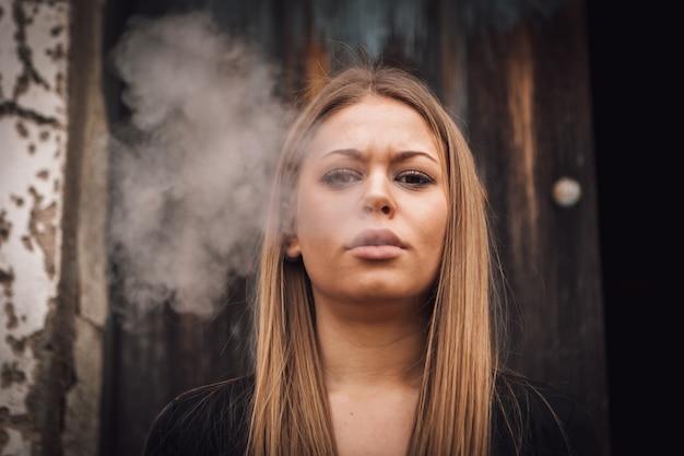 Garota jovem e atraente fumando um charuto