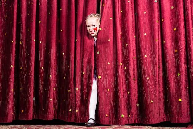 Garota jovem e atraente loira com maquiagem colorida, entrando no palco durante uma peça ou pantomima passando pelas cortinas fechadas