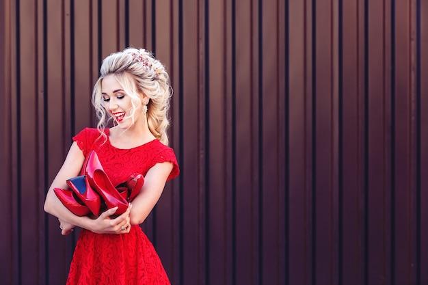 Garota jovem e atraente loira com um vestido vermelho tem nas mãos um monte de sapatos vermelhos. conceito de compras e vendas