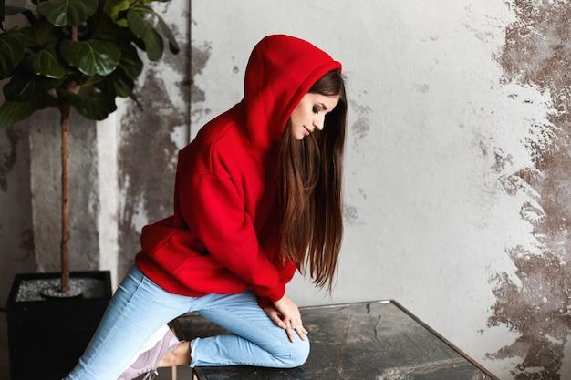 Garota jovem e atraente modelo com um capuz vermelho e calça jeans azul no interior do loft