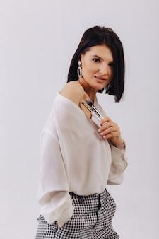 Garota jovem e atraente negócios com pincéis de maquiagem posando na parede lisa. conceito de maquiagem e cosméticos.