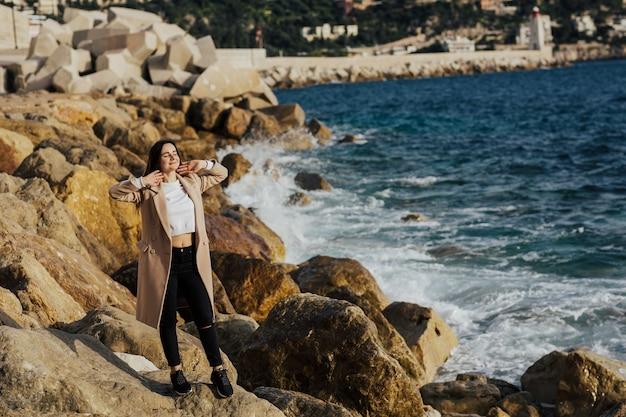 Garota jovem e atraente posando na praia rochosa.