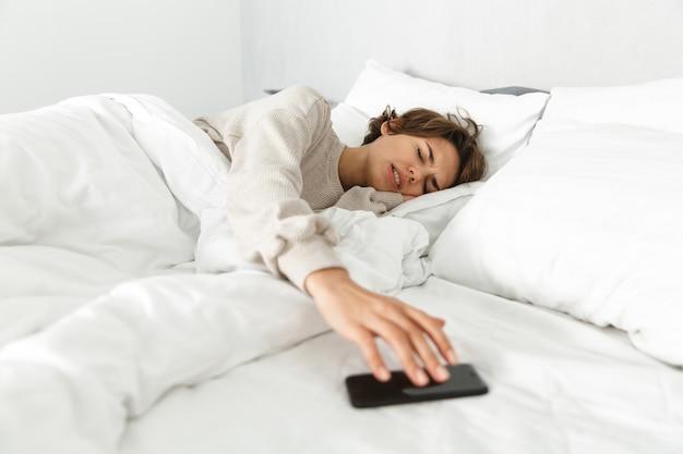 Garota jovem e atraente relaxando na cama pela manhã, pegando o celular