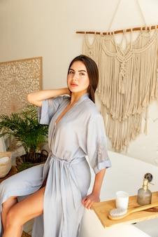 Garota jovem e atraente sentada no banheiro antes de seu procedimento de banho. ela está vestindo um roupão de banho azul.