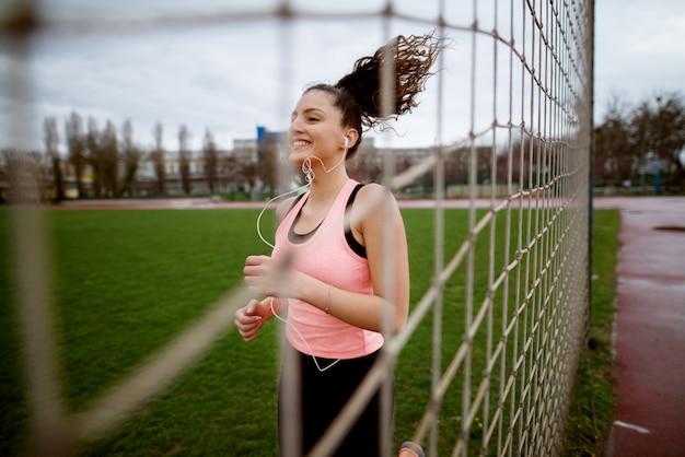 Garota jovem e atraente sorridente fitness correndo com o cabelo girando, imagens através da rede perto do campo de futebol.
