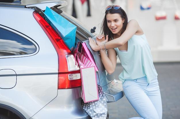 Garota jovem e atraente tentando colocar muitos itens em um carro. mulher colocando sacolas de compras em uma bagagem. jovem fêmea empurrando suas sacolas de compras em um tronco.