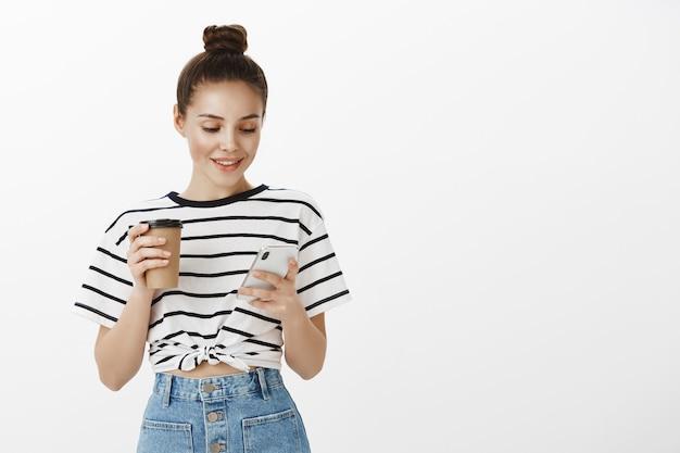 Garota jovem e atraente usando smartphone enquanto bebe café, segurando a xícara e o telefone celular