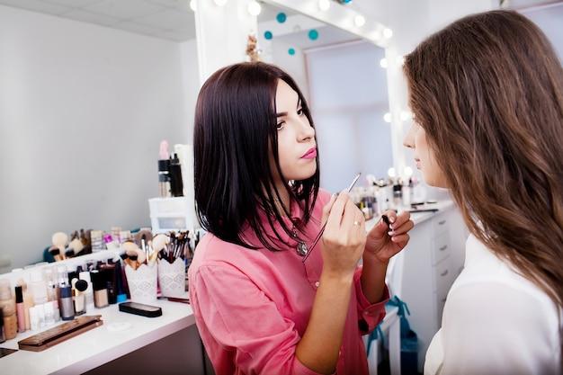 Garota jovem e bonita aplicar maquiagem nas sobrancelhas em um salão de beleza