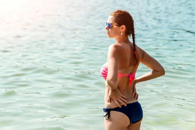 Garota jovem e bonita de biquíni e óculos de sol fica sobre o mar. o de férias, férias, verão, férias, viagens. copyspace.