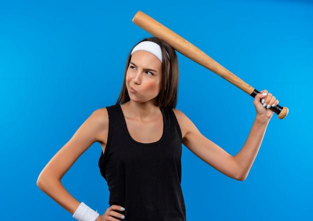 Garota jovem e bonita e confusa, esportiva, usando bandana e pulseira, segurando o taco de beisebol e tocando a cabeça com ele, olhando para o lado com a mão na cintura isolada na parede azul