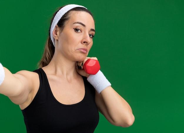 Garota jovem e bonita e confusa, esportiva, usando bandana e pulseiras, segurando um haltere, estendendo a mão em direção à câmera, isolada na parede verde com espaço de cópia