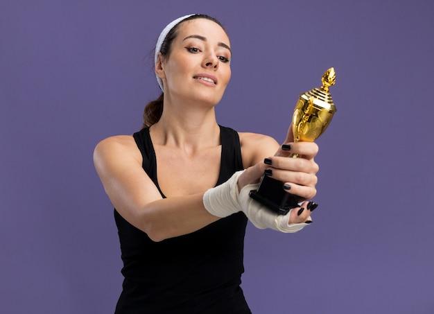 Garota jovem e bonita e esportiva satisfeita usando fita para a cabeça e pulseiras segurando e olhando para a taça do vencedor com o pulso ferido enrolado em bandagem