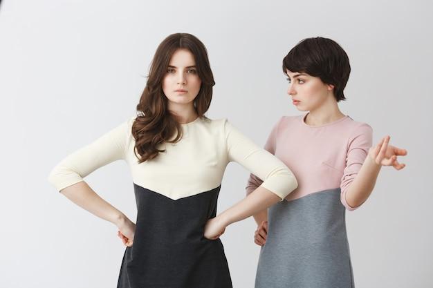 Garota jovem e bonita estudante lésbica discutindo com sua linda namorada de cabelos longos sobre a melhor pose para foto no estande da foto.