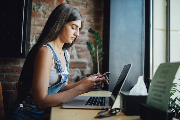 Garota jovem e cansada está sentada no café em frente à janela trabalhando em seu laptop e tomando uma bebida fresca