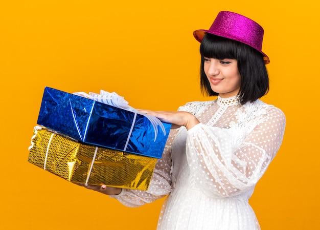 Garota jovem e carrancuda usando chapéu de festa em pé na vista de perfil, segurando e olhando para pacotes de presente isolados na parede laranja