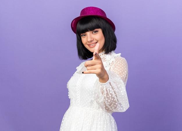 Garota jovem e festeira com chapéu de festa em pé na vista de perfil, olhando e apontando para a frente, isolada na parede roxa com espaço de cópia