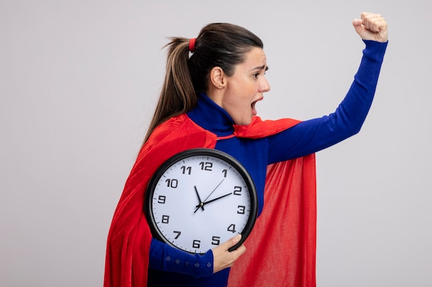 Garota jovem e irritada do super-herói em pé em vista de perfil, segurando o relógio de parede e levantando a mão, isolado no fundo branco