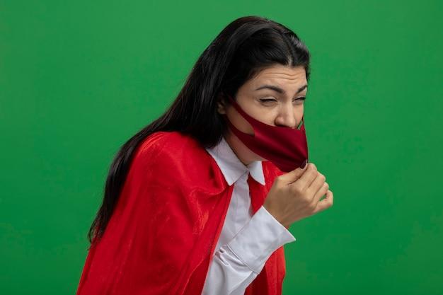 Garota jovem e irritável super-heroína caucasiana em pé na vista de perfil usando uma máscara segurando e tentando tirar a máscara parece distante, isolado em um fundo verde com espaço de cópia