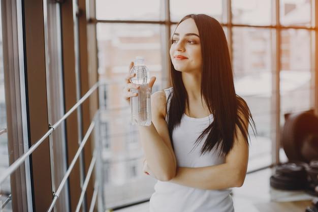 Garota jovem e magra em uma camisa branca e legging cinza em pé em um ginásio com garrafa