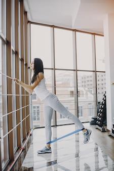 Garota jovem e magra em uma camisa branca e legging cinza engajados em esportes no ginásio