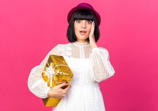 Garota jovem e preocupada com um chapéu de festa segurando um pacote de presente, mantendo a mão no rosto, olhando para a frente, isolada na parede rosa com espaço de cópia