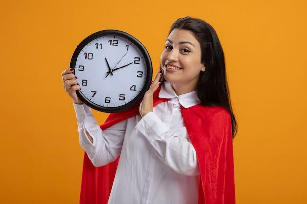 Garota jovem e sorridente super-heroína caucasiana segurando um relógio olhando para a câmera isolada em um fundo laranja com espaço de cópia