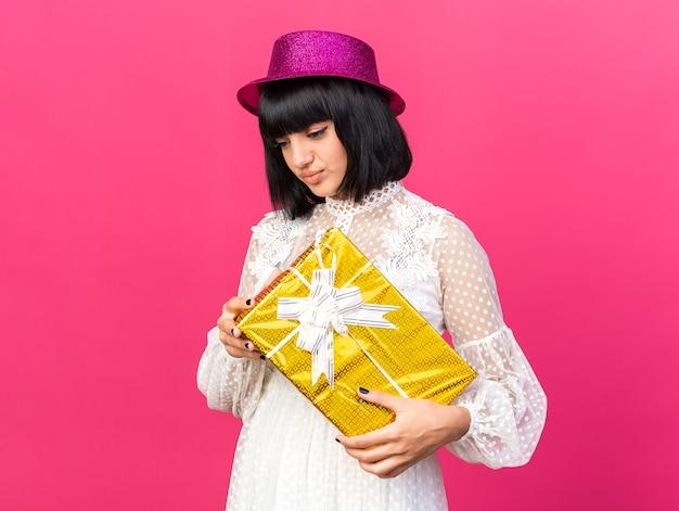 Garota jovem e triste com um chapéu de festa segurando um pacote de presente olhando para baixo com os lábios franzidos, isolados na parede rosa com espaço de cópia