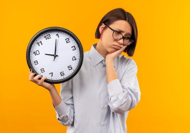 Garota jovem e triste de call center usando óculos, segurando um relógio, colocando a mão na bochecha e olhando para baixo, isolada na parede laranja