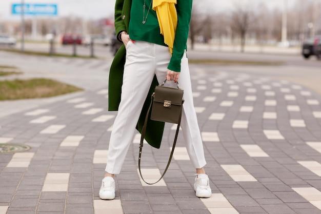 Garota jovem, elegante, de calça branca, casaco de verdes quentes
