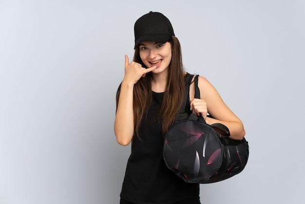 Garota jovem esporte com bolsa esporte isolada em cinza fazendo gesto de telefone. ligue-me de volta sinal