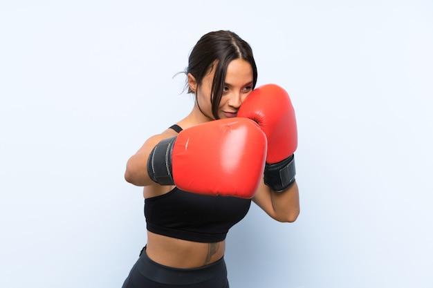Garota jovem esporte com luvas de boxe sobre fundo azul isolado
