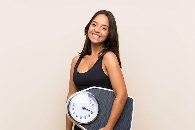 Garota jovem esporte com máquina de pesagem