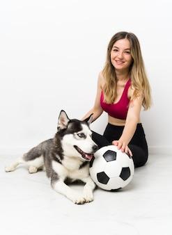 Garota jovem esporte com seu cachorro sentado no chão