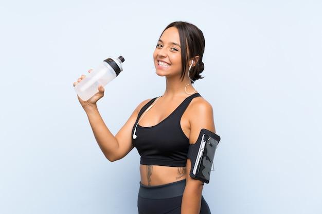 Garota jovem esporte com uma garrafa de água sobre a parede azul isolada