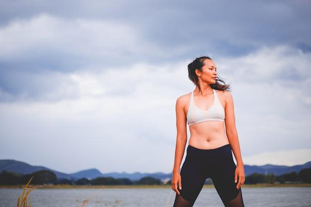 Garota jovem esporte faz yoga no parque, mulher de beleza asiática